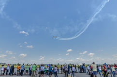 Stunt planes in the sky. Group of people looking at four aerobatics aircrafts flying at the Bucharest Air Show on June 22, 2014 in Bucharest, Romania.nThe Stock Image