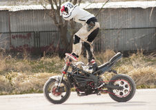 Stunt riding a motorcycle standing. Stock Image