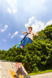 Stunt scooter rider gets air off. Teen boy gets air off of a Quarter pipe with his stunt scooter Royalty Free Stock Image