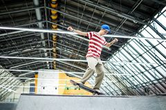 Stunt on skateboard. Casual teenage guy standing on skateboard while practicing parkour stunt on special area or stadium royalty free stock photography