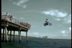 Stuntman drijfmotorfiets van pijler in oceaan stock footage