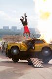 Stuntman fliegt über das brennende Auto Stockfoto