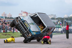 Stuntman lie under to passing a car on two wheels. MOSCOW - AUG 25: Stuntman lie under to passing a car on two wheels on Festival of art and film stunt Stock Photos