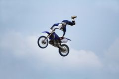 Stuntman on motorcycle. A stunt biker performing an acrobatic figure in the sky Royalty Free Stock Photo