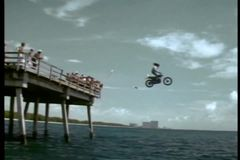 Stuntman napędowy motocykl z mola w ocean zbiory