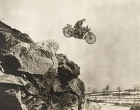 Stuntman On Motorbike Flying Over Cliff Royalty Free Stock Photos