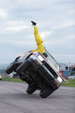 Stuntman stands upside down on a car traveling on two wheels Stock Images