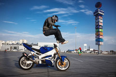 Stuntriding acid drop. Biker performs a trick on Motorcycles Stock Photos