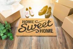 Stuoia benvenuta della casa dolce casa, scatole commoventi, femmina e scarpe del maschio fotografia stock