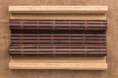 Stuoia di bambù scura e leggera sotto forma di bugia del rotolo sulla tela da imballaggio immagini stock libere da diritti