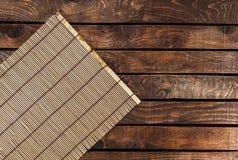 Stuoia di bambù sulla tavola di legno fotografia stock libera da diritti
