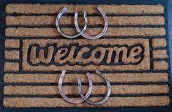 Stuoia di porta benvenuta con i ferri di cavallo Immagine Stock