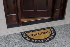 Stuoia di porta benvenuta con la porta aperta Fotografia Stock Libera da Diritti