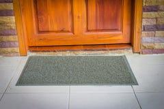 Stuoia di porta grigia con la porta vicina Fotografia Stock