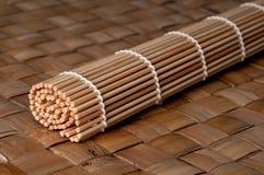 Stuoia di rotolamento dei sushi su una stuoia di posto di bambù Fotografia Stock