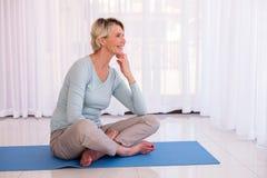 Stuoia di seduta di yoga della donna immagini stock