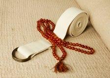 Stuoia di yoga con i rosari e la cinghia Fotografia Stock