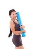 Stuoia di yoga della tenuta della donna di forma fisica Fotografia Stock