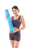 Stuoia di yoga della tenuta della donna di forma fisica Immagine Stock