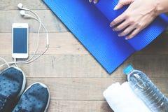 Stuoia piegante di yoga della mano della donna sul pavimento di legno, allenamento con il concetto Fotografia Stock Libera da Diritti