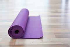 Stuoia porpora di yoga sul pavimento di legno Immagini Stock
