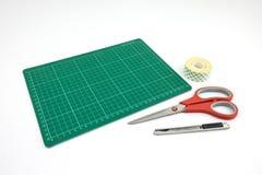Stuoia verde di taglio con il rotolo di forbici e del nastro della taglierina di doppio fotografia stock libera da diritti
