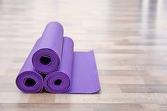 Stuoie porpora di yoga sul pavimento di legno Fotografia Stock Libera da Diritti