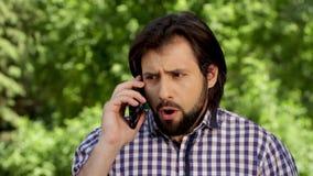 Stupéfait et distrait équipez-nous parlant au téléphone Il a une querelle Le type tient le téléphone près de l'oreille droite et  banque de vidéos