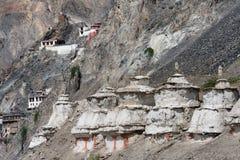 Stupa antique bouddhiste blanc sur la pente grise de la montagne, plus haut vers le haut de la pente des ruines du monastère, le  Photographie stock libre de droits