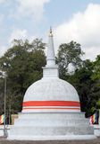 Stupa at Anuradhapura. A small white stupa at Anuradhapura, surrounded by buddhist flags and an orange ribbon Stock Images