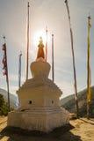 Stupa avec des drapeaux de prière dans le coucher du soleil Images stock