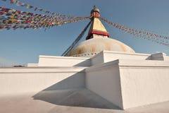 Stupa blanco como la nieve antiguo de Bodnath en fondo del cielo azul, adornado con las banderas budistas del rezo, Katmandu, Nep Fotos de archivo