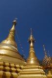 Stupa, chedi e pagode dourados no templo budista em Tailândia com fundo do céu azul Fotografia de Stock Royalty Free