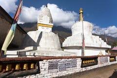 Stupa con le bandiere e le ruote di preghiera Fotografie Stock