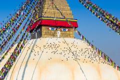 Stupa di Bodhnath a Kathmandu con gli occhi di Buddha e le bandiere di preghiera Fotografia Stock