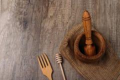 stupa en stamper op jute op de dorpslijst keukengerei verbrijzeling vork en stok voor honing de hand eco-vriend van de kruidterug royalty-vrije stock fotografie