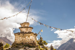 Stupa at the mountain with nepalese flags. View from the trekking at Annapurnas circuit, Himalaya, Nepal Royalty Free Stock Photography