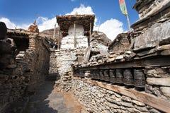 Stupa och vägg för bönhjul i den Manang villlagen royaltyfri bild