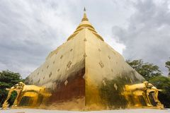 Symmetrical golden elephants in Buddhist temple. Stupa pyramid with golden elephants statues under a dramatic sky at the Wat Phra Singh temple, Chiang Mai Stock Image