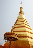 Stupa. Shiny golden buddhism stupa the WAT PHRA THAT CHO HAE CHEDI in PHRAE province in northern THAILAND with white golden color umbrella in a small north THAI Stock Photo