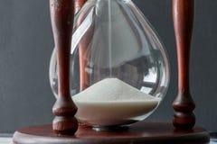 Stupad vit sandkristall i tappningträtimglas med blurr Arkivfoton