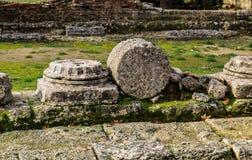 Stupade pelare fördärvar in av Olympia Greece med forntida förberedande stenar i förgrunden och en spillrorvägg bakom jpg Arkivbild