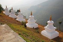Stupas blanc majestueux donnent sur des montagnes au Bhutan images libres de droits