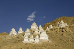 Stupas bouddhistes de temples blancs sur la pente d'une montagne de désert sous un ciel bleu avec les nuages blancs images libres de droits