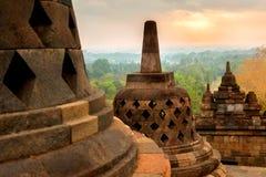 Stupas budistas de piedra enormes contra la perspectiva de la salida del sol en el templo de Borobudur Java Island indonesia Hist fotos de archivo libres de regalías