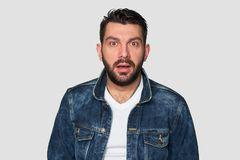 Stupefied bearded man looks with astonishment into camera. Handsome guy wearing denim clothes. Surprised emotional hipster. Facial expression Royalty Free Stock Photo