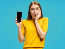 Stupefied girl opens eyes and mouth widely, holds a phone. Photo of young girl with surprised expression in yellow sweater on blue background. Omg concept stock image