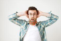 Stupefied surprised man with long beard dressed in fashionable clothes, keeps hand on head, stares through spectacles. Being amazed to hear shocking news Royalty Free Stock Image