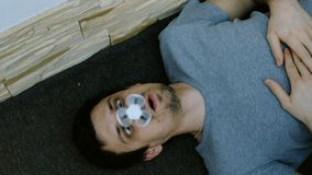 Stupid fool of a man lying on the floor and turns on the nose spinner. 4K.  stock video