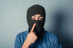 Stupid man wearing a balaclava. A stupid man wearing a balaclava is trying to pick his nose stock image